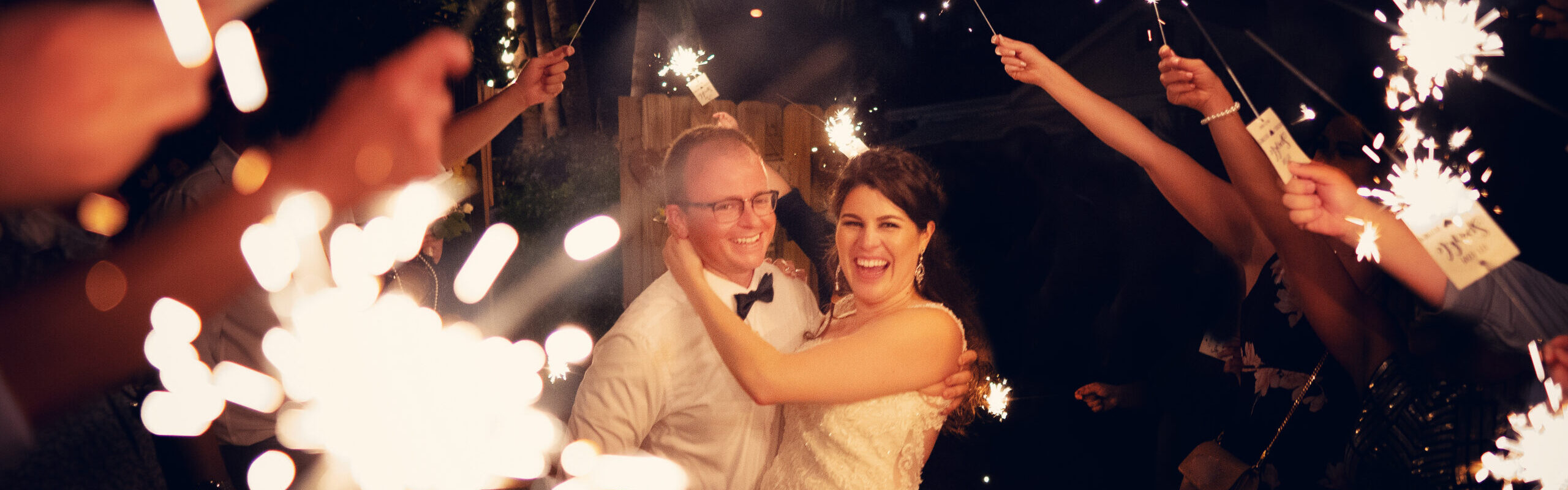 Newlyweds walking among sparkle lights on their wedding day